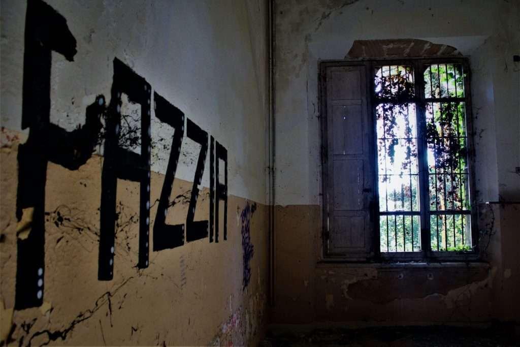 """Graffito """"PAZZIA"""" all'interno del padiglione Ferri"""